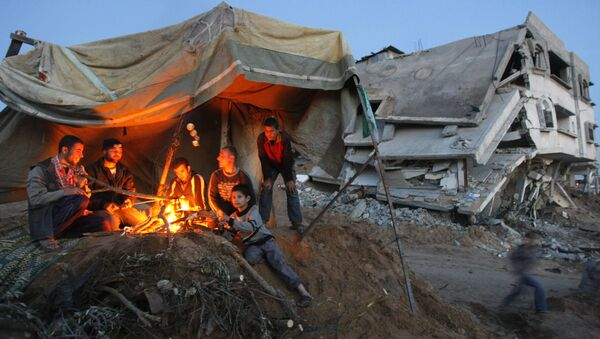 Palestinians sit around a fire under the cover of a tent on the ruins of their home - Sputnik International