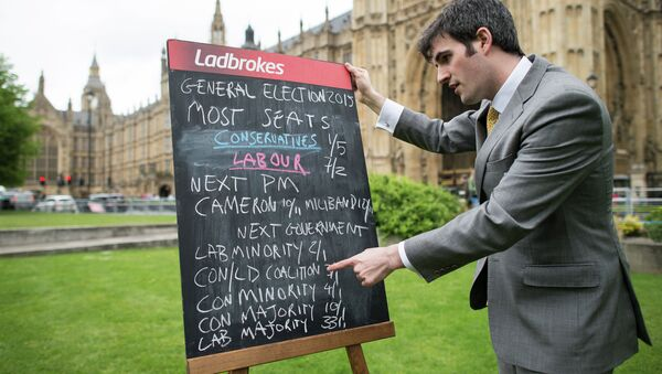 A bookmaker displays the latest odds on the result of the upcoming UK general election outside the Houses of Parliament in central London on May 6, 2015 - Sputnik International