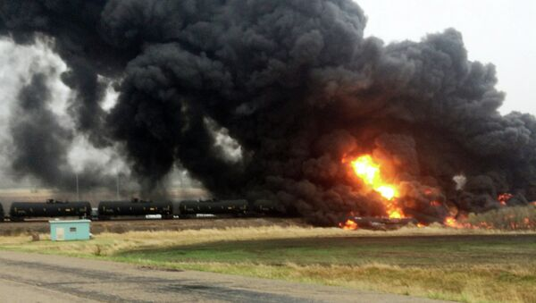 Smoke and fire rise from an oil train that derailed, Wednesday, May 6, 2015, in Heimdal, N.D. - Sputnik International