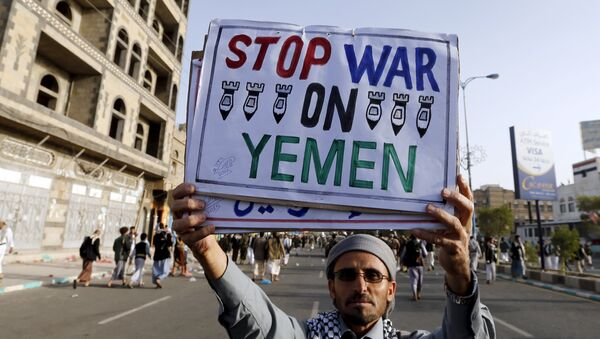 A follower of the Houthi group holds up a sign at the site of a demonstration against the air strikes by the Saudi-led coalition in Sanaa April 27, 2015 - Sputnik International