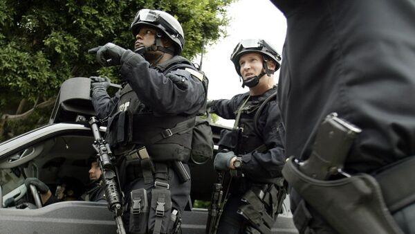 FBI agents in riot gear get information from a Los Angeles Police Department police officer (R) as they head towards the Mexican consulate in Los Angeles - Sputnik International