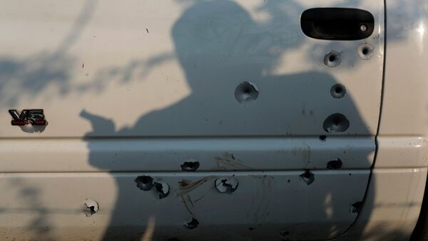 The shadow of a member of the United Front for Security and Development of the State of Guerrero (FUSDEG) vigilante group is seen before a bullet-riddled truck March 31, 2015 at San Juan del Reparo, Guerrero State, Mexico - Sputnik International