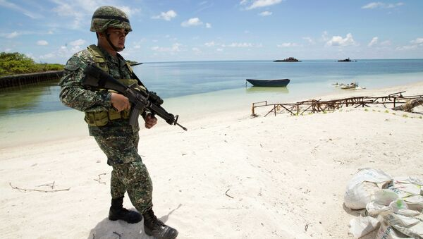 A Filipino soldier patrols the shore of disputed Pag-asa Island in the South China Sea. - Sputnik International