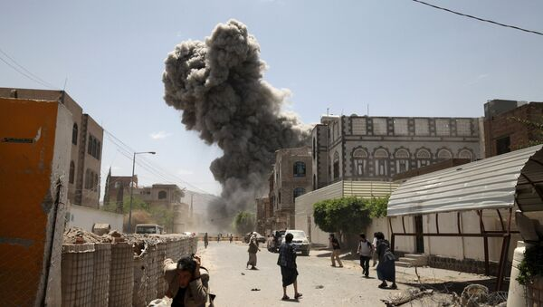 People flee as smoke billows after air strikes hit the house of Yemen's former President Ali Abdullah Saleh in Sanaa May 10, 2015 - Sputnik International