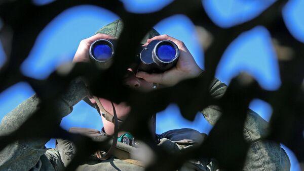 Russian soldier looking through binoculars during military exercise in the Kaliningrad Region. File photo. - Sputnik International