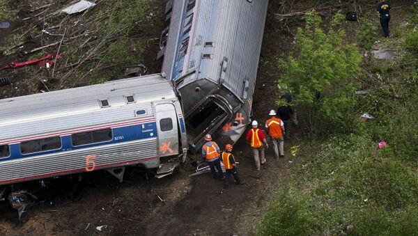 Emergency workers and Amtrak personnel inspect a derailed Amtrak train in Philadelphia, Pennsylvania May 13, 2015 - Sputnik International