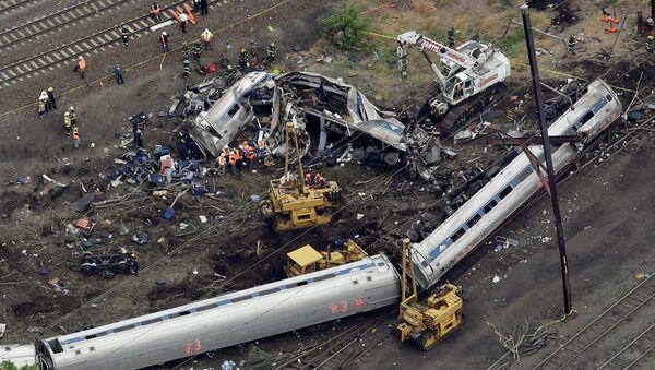 Emergency personnel work at the scene of a deadly train derailment, Wednesday, May 13, 2015, in Philadelphia - Sputnik International