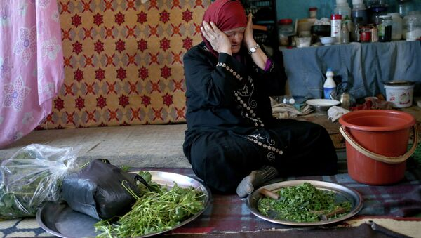 Syrian refugee Ruwaida al-Ahmad, 45, weeps while preparing to cook grass as she tells her story to the Associated Press inside her room that used to be a classroom at the Al-Rama Public School that has become home to 22 Syrian families at the Lebanese-Syrian border village of Al-Rama, north Lebanon - Sputnik International