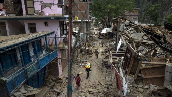 Local residents walk past collapsed buildings after Tuesday's earthquake at Singati Village, in Dolakha, Nepal, May 15, 2015 - Sputnik International