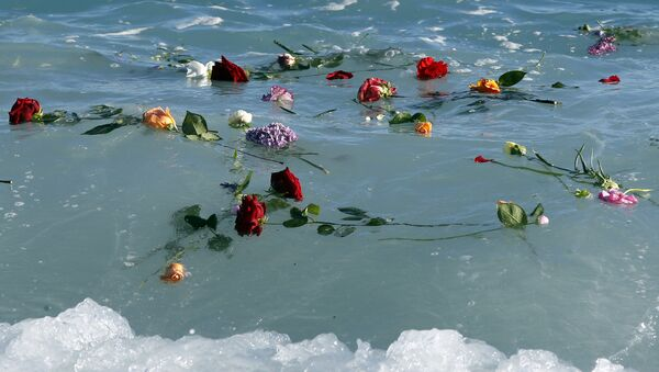 Flowers float in the sea after they were thrown into the Mediterranean in honor of the migrants lost making the perilous journey across the sea, on April 28, 2015 in Nice, southeastern France - Sputnik International