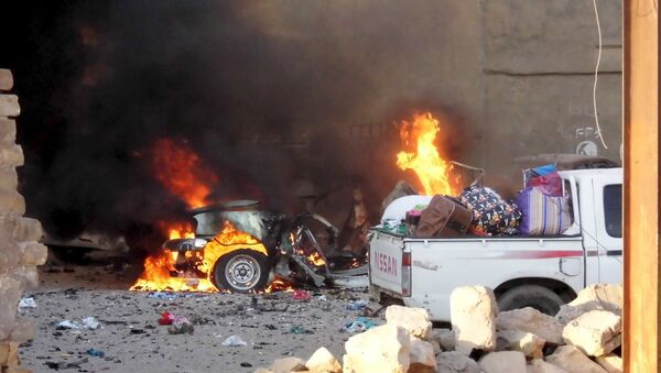 A car is engulfed by flames during clashes in the city of Ramadi, May 16, 2015 - Sputnik International