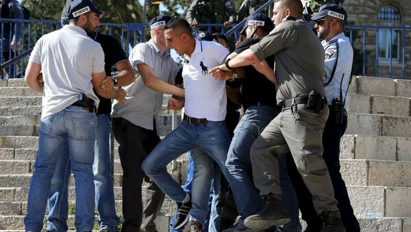 Israeli police officers scuffle with a Palestinian protester (C) as they disperse a protest near Damascus Gate outside Jerusalem's Old City, during a march marking Jerusalem Day, May 17, 2015 - Sputnik International