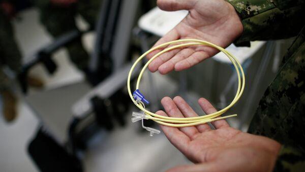 U.S. Navy medical personnel displays an internal feeding tube, used for force-feeding detainees. - Sputnik International