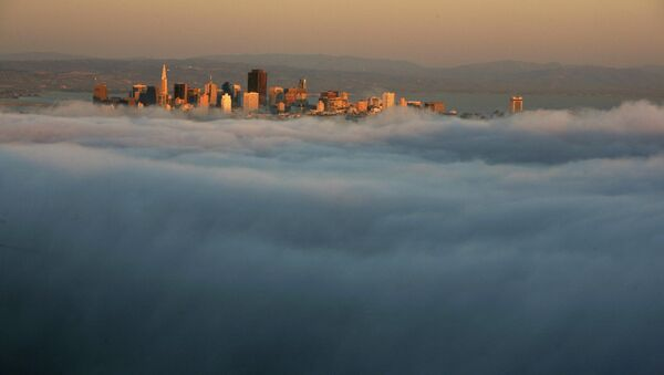 The skyline of San Francisco appears above the evening fog as the suns sets on the Marin Headlands in Sausalito, California - Sputnik International