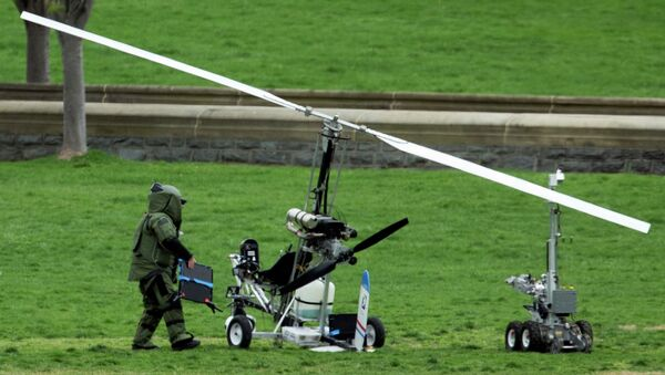 A member of a bomb squad checks a small helicopter after a man landed on the West Lawn of the Capitol in Washington, Wednesday, April 15, 2015. - Sputnik International