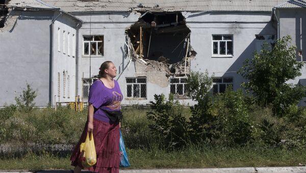 A woman walks past a damaged school in the city of Lisichansk, Luhansk region, eastern Ukraine - Sputnik International