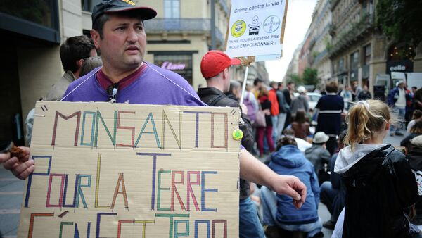 An activist holds a banner that reads 'Monsanto pour la terre c'en est trop' (Monsanto, too much for the earth) at a march against Monsanto, where 'anti-OGM31' cooperative and citizens are protesting against US agriculture and seed giant Monsanto on May 23, 2015, in Toulouse - Sputnik International