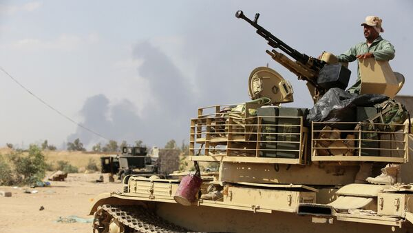 An Iraqi army member mans a tank on the outskirts of Baiji refinery north of Tikrit, during a joint operation between the army and popular mobilisation units to retake the remaining area of the Baiji oil refinery from Islamic State (IS) group jihadists, on May 24, 2015 - Sputnik International