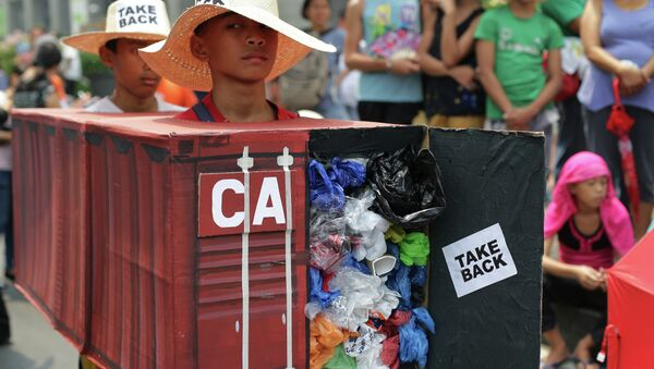 Filipino environmental activists wear a mock container vans filled with garbage to symbolize the 50 containers of waste that were shipped from Canada to the Philippines two years ago, as they hold a protest outside the Canadian embassy at the financial district of Makati, south of Manila, Philippines on Thursday, May 7, 2015 - Sputnik International