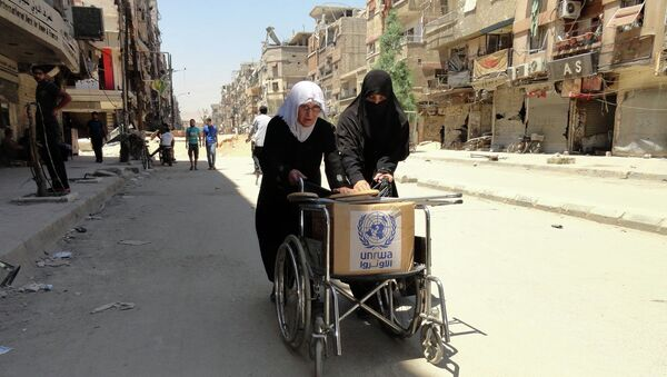 Residents of Syria's Yarmuk Palestinian refugee camp, south of Damascus, use a wheelchair to carry a box of goods distributed by the United Nations Relief and Works Agency (UNRWA) on July 17, 2014 - Sputnik International