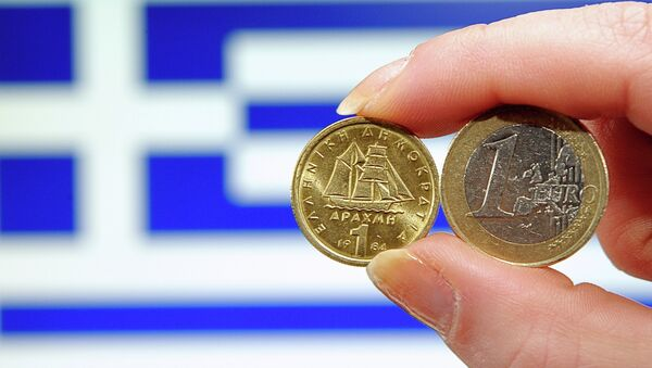 A person holding a 1 euro coin (R) and Greek 1 drachma coin in front of a Greek national flag - Sputnik International