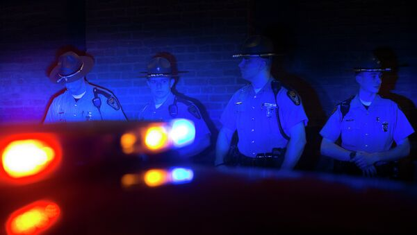 Police officers are illuminated by patrol car lights during a protest against the acquittal of Michael Brelo, a patrolman charged in the shooting deaths of two unarmed suspects. - Sputnik International