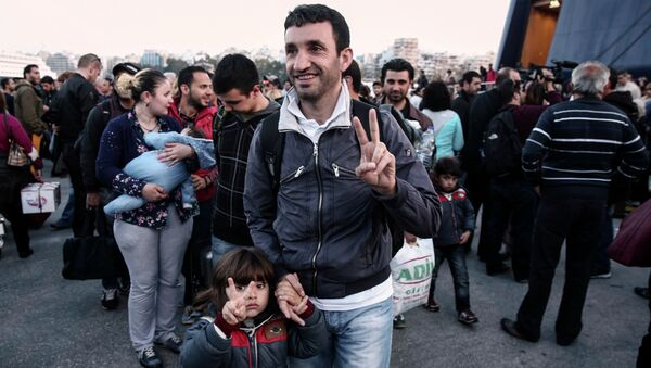 A migrant from Syria and his child flash a victory sign as they arrive from the eastern Aegean island of Lesvos at the port of Piraeus, near Athens - Sputnik International