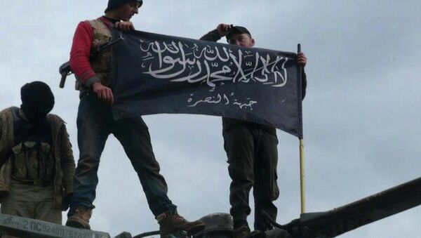 Rebels from al-Qaida-affiliated Jabhat al-Nusra, also known as the Nusra Front, wave their brigade flag, as they step on the top of a Syrian air force helicopter. - Sputnik International