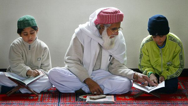 An Iman helps a young boy learn The Koran at The Central Mosque in Luton - Sputnik International