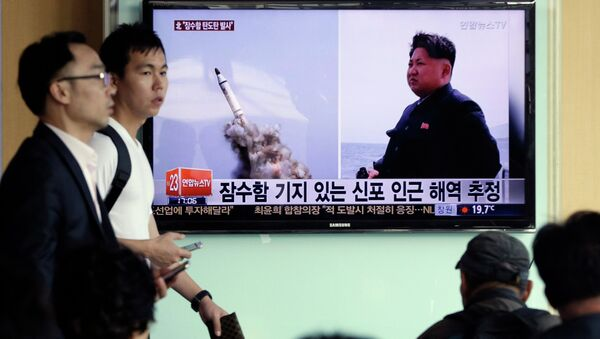 South Korean men pass by a TV news program showing images published in North Korea's Rodong Sinmun newspaper of North Korea's ballistic missile believed to have been launched from underwater and North Korean leader Kim Jong-un, at Seoul Railway station in Seoul, South Korea, Saturday, May 9, 2015 - Sputnik International