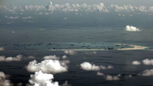 An aerial file photo taken though a glass window of a Philippine military plane shows the alleged land reclamation by China on Mischief Reef in the Spratly Islands in the South China Sea, west of Palawan, Philippines, May 11, 2015 - Sputnik International
