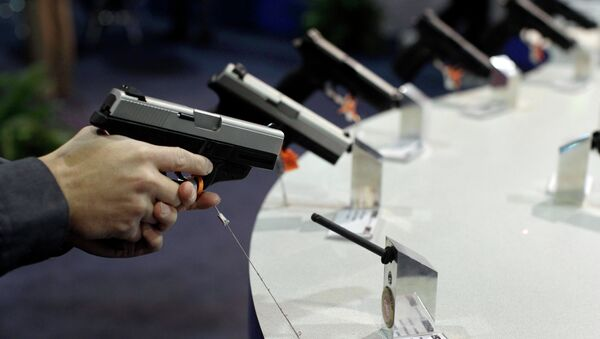 A firearms retailer examines a Smith & Wesson 9mm pistol at the Shooting, Hunting and Outdoor Trade show, Jan. 18, 2011, in Las Vegas - Sputnik International