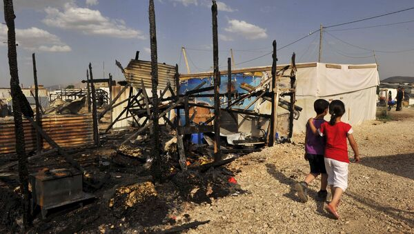 Children walk near the remains of tents that were burnt in a refugee camp for Syrian refugees in Lebanon's Bekaa Valley June 1, 2015. - Sputnik International