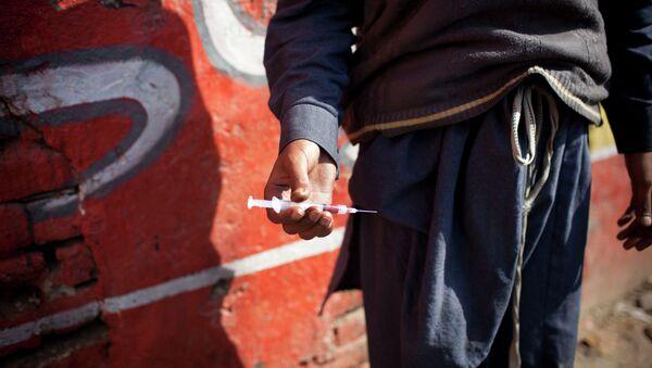 A drug addict holds a needle and syringe. - Sputnik International