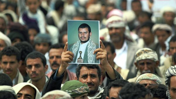 A Yemeni Shiite man holds up a picture of the Shiite movement leader Abdul-Malik al-Houthi during a demonstration organized by the Shiite Huthi movement to demand the government to rescind a decision to curb fuel subsidies on August 20, 2014 - Sputnik International