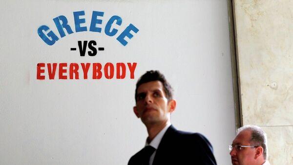 Pedestrians walk past stenciled graffiti on a wall outside of a bank in Athens. - Sputnik International