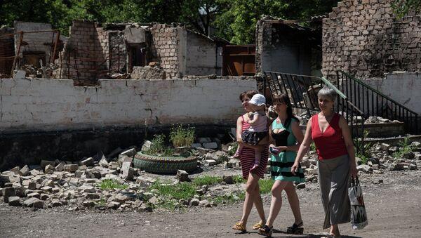 Residents walk in front of destroyed building as a result of shelling on June 8, 2015 in Novotoshkivske village, Donetsk region - Sputnik International