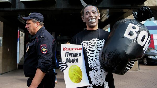 Russian Communist Party activist, wearing a mask depicting US President Barack Obama, holds a poster reading Nobel Peace Prize in one hand and a bag reading War in the other, takes part at a picket outside the UN mission in Moscow, Russia, Tuesday, Sept. 9, 2014 - Sputnik International