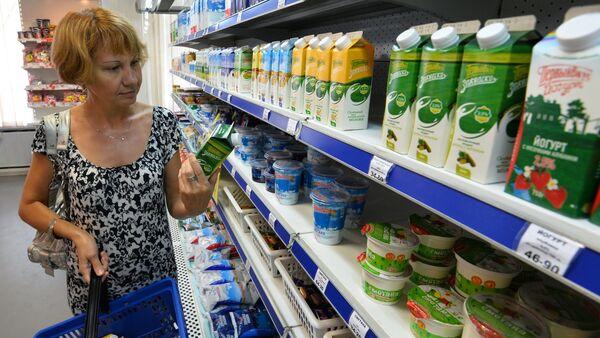 A buyer near the shelf with dairy products - Sputnik International