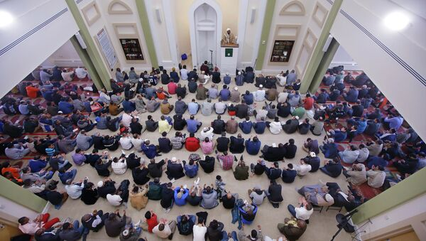 Muslim men sit on their prayer rug as visiting Imam Muhammad Adeyinka Mendes delivers his sermon before prayers in the mosque at the Islamic Society of Boston Cultural Center Friday, April 24, 2015, in Boston - Sputnik International
