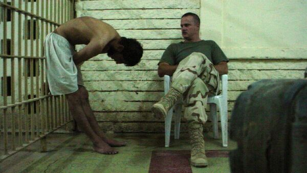 This is an image obtained by The Associated Press which shows a detainee bent over with his hands on the bars of a prison cell watched by a soldier in late 2003 at the Abu Ghraib prison in Baghdad, Iraq - Sputnik International