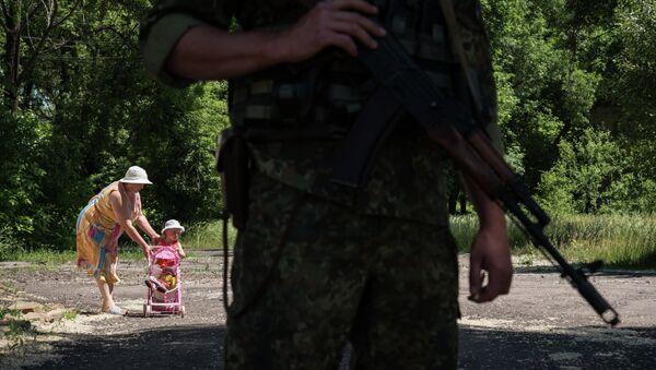 Woman walks with her child as Ukrainian serviceman stands guard on June 8, 2015 in Novotoshkivske village, Donetsk region - Sputnik International