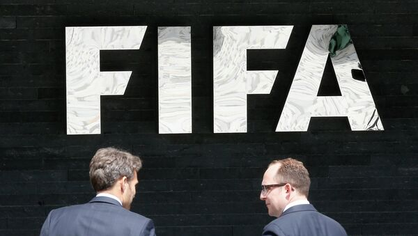 Two men talk to each other in front of the FIFA logo at the FIFA headquarters in Zurich, Switzerland, Wednesday, May 27, 2015 - Sputnik International