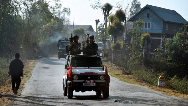 In this photograph taken on February 18, 2012, a vehicle carrying armed security personnel passes along a road on the outskirts of Imphal in the north eastern Indian state of Manipur - Sputnik International