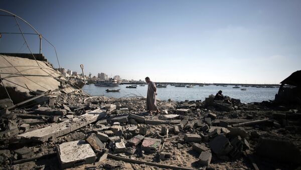 A Palestinian man inspects the damage of a police post, following an Israeli missile strike killing four boys from the same extended Bakr family, in Gaza City, Wednesday, July 16, 2014. - Sputnik International