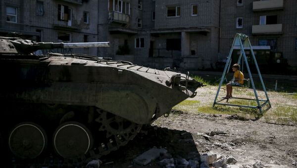 A boy sits on a swing near a building, which was damaged during fighting between Kiev and Donbass forces, as an armoured personnel carrier (APC) of the Ukrainian armed forces is seen nearby in Avdeyevka near Donetsk. June 7, 2015. - Sputnik International