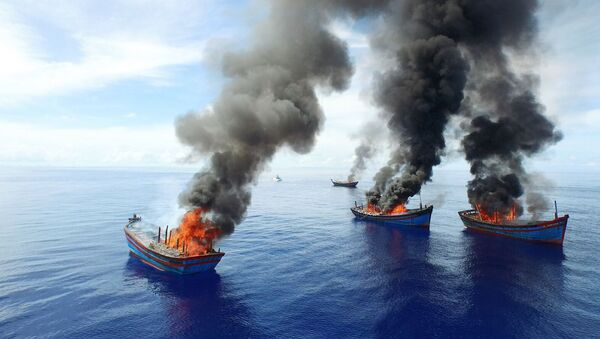 Columns of black smoke rise from four Vietnamese boats in the waters off Palau. - Sputnik International
