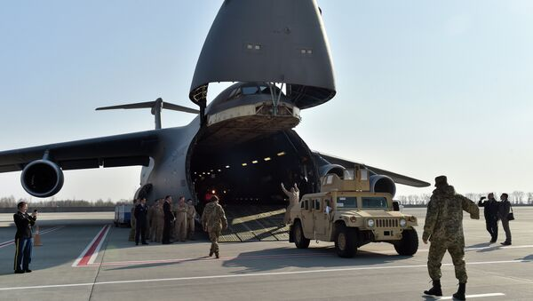 Ukrainian and US servicemen unload armoured cars from a plane at Kiev airport on March 25, 2015 during a welcoming ceremony of the first US plane delivery of non-lethal aid, including 10 Humvee vehicles - Sputnik International