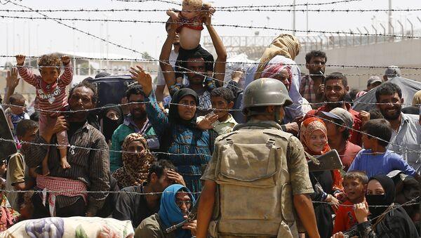 Syrian refugees wait behind the border fences to cross into Turkey at Akcakale border gate in Sanliurfa province, Turkey, June 15, 2015 - Sputnik International