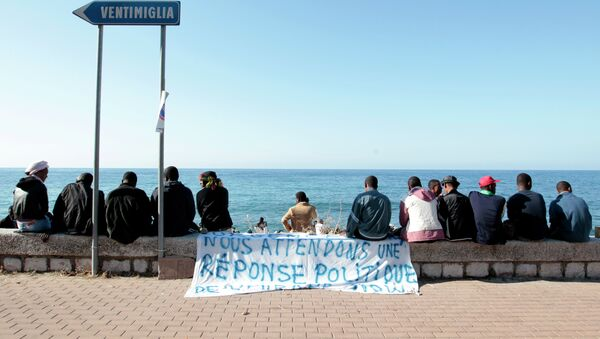 Migrants sit near a banner reading We are waiting fo a political response on the shores of the Mediterranean sea in the Italian Franco-Italian border city of Ventimiglia on June 15, 2015, as they wait to cross into France - Sputnik International